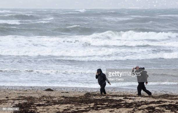 People walk in the wind beside the beach in St Mount's Bay near Penzance as the effects of Hurricane Ophelia begin to be felt on the west coast of...