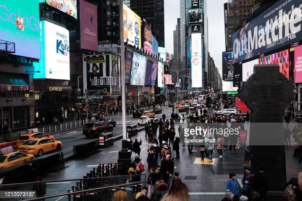 People walk in Times Square in Manhattan on March 12 2020 in New York City New York City's Broadway theaters will need to close by 5 pm Thursday...