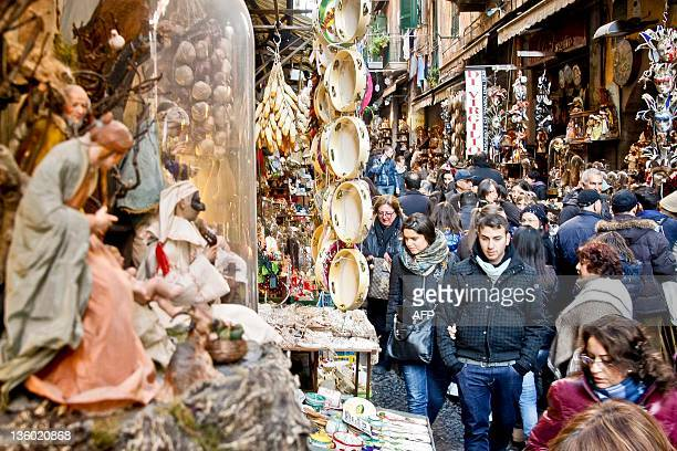 People walk in Via San Gregorio Armeno in Naples which hosts many artisans who make world renowed hand-crafted Nativity scenes on December 20, 2011....