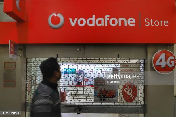 People walk infront of a Vodafone Mobile service Operator Showroom in New Delhi, India, on 7 March 2019.