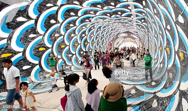People walk inside the 60meterlong giant carp streamers during the Japan fairy story festival on May 5 2015 in Kusu Oita Japan