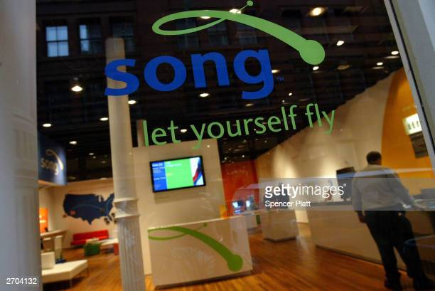 People walk inside the new 'Song in the City' airline store November 6 2003 in New York City Song a new lowfare division of Delta Air lines has...