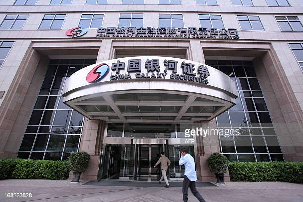 People walk into a China Galaxy Securities office building in Beijing on May 7 2013 Two Chinese stateowned firms will hold initial public offerings...