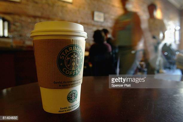 People walk into a Starbucks coffee shop October 5 2004 in New York City As coffee bean costs in the US have risen in the past two months the...