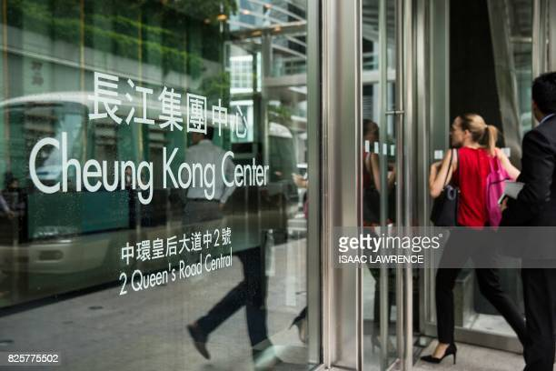 People walk into Cheung Kong Center headquarters of CK Hutchinson Holdings in the Central district of Hong Kong on August 3 2017 CK Hutchinson will...