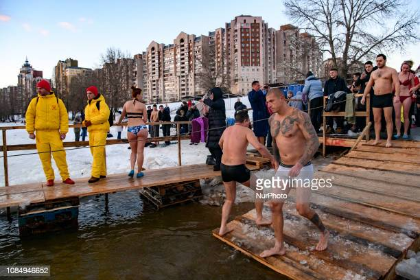 People walk into icy waters to take a dip during celebrations of the Orthodox Christian feast of Epiphany in Kyiv Ukraine January 19 2019
