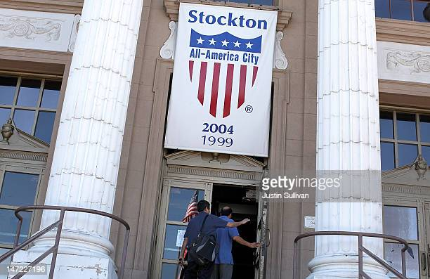 People walk into Stockton City Hall on June 27, 2012 in Stockton, California. Members of the Stockton city council voted 6-1 on Tuesday to adopt a...
