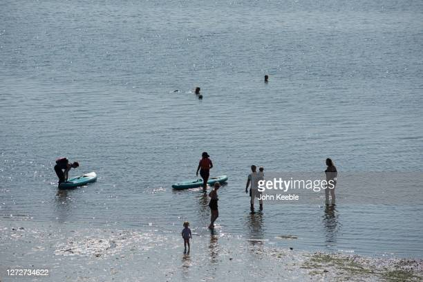 People walk into the sea from the beach on September 14 2020 in Southend on Sea England Parts of the UK are expected to hit 29 degrees celsius as the...