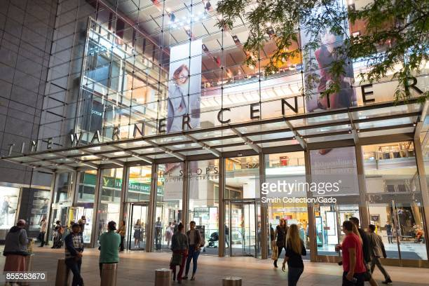 People walk into Time Warner Center an upscale shopping mall at Columbus Circle in Manhattan New York City New York at night with sign and windows...