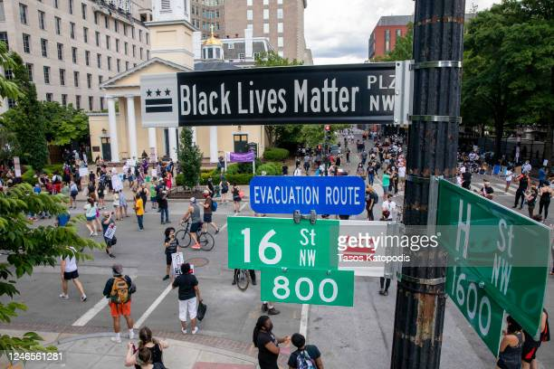 People walk near 16th and H street after volunteers with permission from the city painted Black Lives Matter on the street near the White House on...