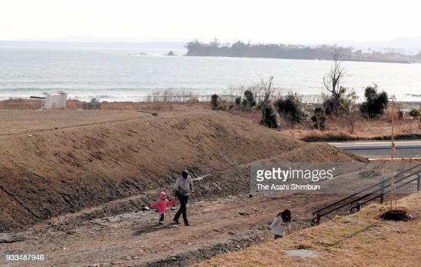 People walk near a beach on the 7th anniversary of the Great East Japan Earthquake on March 11 2018 in Kesennuma Miyagi Japan The death toll from the...