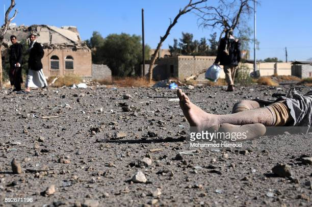 People walk near a body of a prisoner after he was killed in airstrikes targeted the prison on December 13 2017 in Sana'a Yemen More than 12...