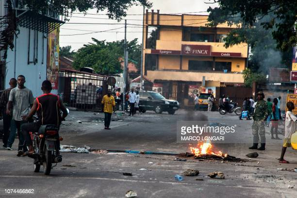 People walk near a burning heap of trash set on fire by supporters of the Democratic Republic of Congo's Union for Democracy and Social Progress...