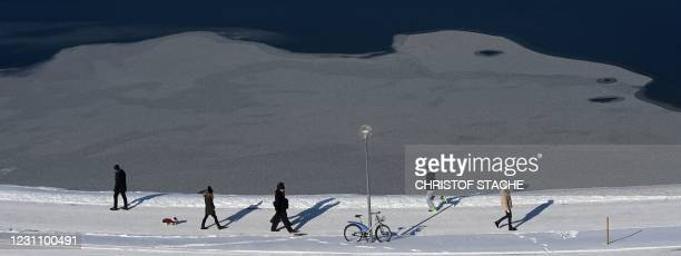 People walk near a ice floe in the Olympic park in Munich, southern Germany, during nice winter weather with temperatures by minus five degrees on...