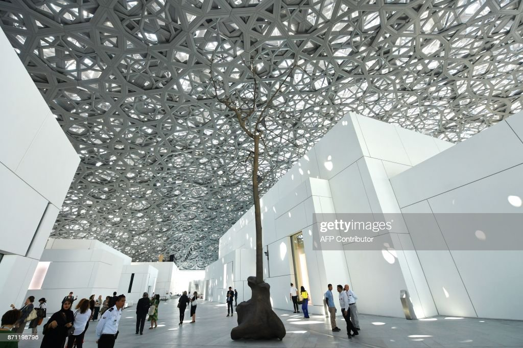 People walk near a sculpture by Italian artist Giuseppe Penone at the Louvre Abu Dhabi Museum on November 7, 2017, on the eve of the official opening of the museum on Saadiyat island in the Emirati capital. More than a decade in the making, the Louvre Abu Dhabi opens its doors this week, bringing the famed name to the Arab world for the first time. The museum currently has some 300 pieces on loan, including an 1887 self-portrait by Vincent van Gogh and Leonardo da Vinci's 'La Belle Ferronniere'. CAPTION