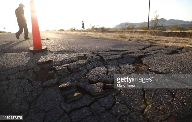 People walk near cracks in the road after a 64 magnitude earthquake struck the area on July 4 2019 near Ridgecrest California The earthquake was the...