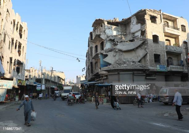 People walk near heavily damaged buildings in the rebel-held city of Idlib in northwestern Syria on September 16, 2019. - A deal Moscow and Ankara...