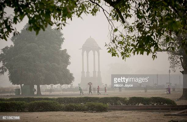 People walk near India gate amid heavy dust and smog November 7 2016 in Delhi India People in India's capital city are struggling with heavily...
