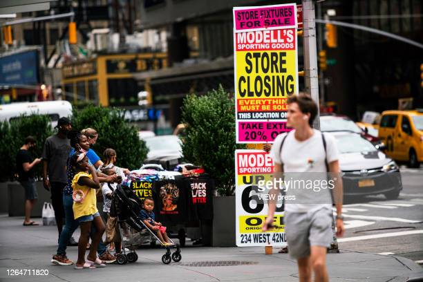 People walk near posters of a retail store closing in Times Square on August 8 2020 in New York City With more than four months NYC has closed some...