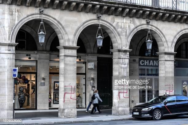 People walk near swastikas spray painted on columns of the Rivoli street in central Paris on October 11, 2020.