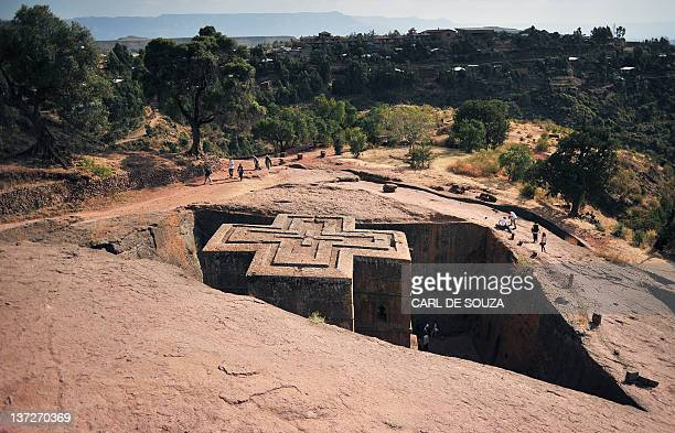 People walk near the ancient rockhewn church of Bete Giyorgis in Lalibela Ethiopia on January 18 2012 Ethiopian monks and priests are preparing for...