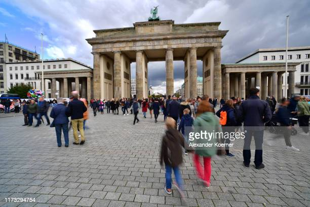 People walk near the Brandenburg Gate during celebrations on German Unity Day on October 3, 2019 in Berlin, Germany. The day marks the 1990...