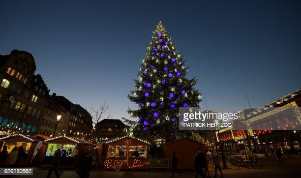 People walk near the Christmas tree during the traditional Christmas market in Strasbourg eastern France on November 28 2016 / AFP / PATRICK HERTZOG