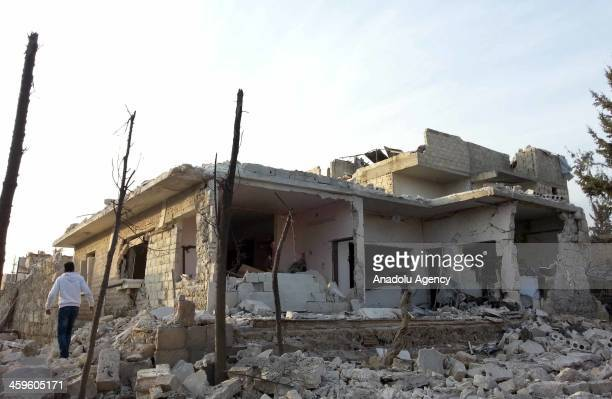 People walk near the destroyed houses in Azaz town of Aleppo, Syria, December 28, 2013. Four people were killed and many others were wounded in the...