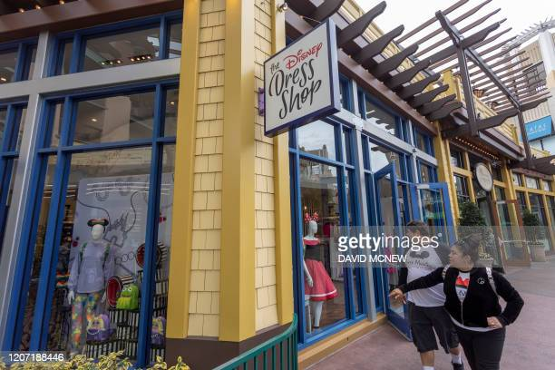 People walk near the Disney Dress Shop in Downtown Disney District shopping mall which remains open on the first day of the closure of Disneyland and...