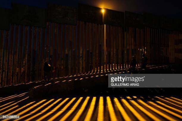 TOPSHOT People walk near the fence in Mexican side of the Mexico US border on April 5 at Playas de Tijuana northwestern Mexico The Pentagon said on...