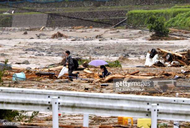 People walk near the flooded river as torrential rain hit on July 6 2017 in Asakura Fukuoka Japan Two people died and six others were missing in...