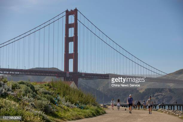 People walk near the Golden Gate Bridge amid the coronavirus outbreak on April 27, 2020 in San Francisco, California. The Coronavirus pandemic has...