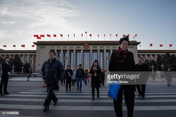 People walk near the Great Hall of the People after the Second Plenary Meeting of the National People's Congress, on March 9, 2016 in Beijing, China....