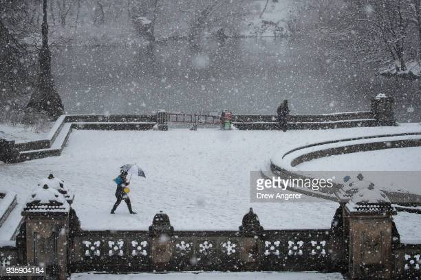 People walk near The Lake in Central Park during a snowstorm March 21 2018 in New York City The fourth nor'easter in three weeks hit the city on...