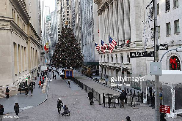 People walk near the New York Stock Exchange on December 19 2016 in New York City Markets rose modestly in morning trading as the Dow Jones...