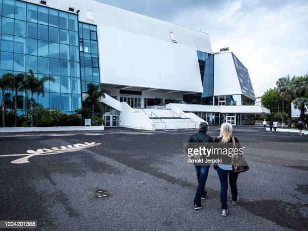 People walk near the Palais des Festivals on May 11, 2020 in Cannes, France. The 73rd Cannes Film festival was due to start on May 12, but due to the...