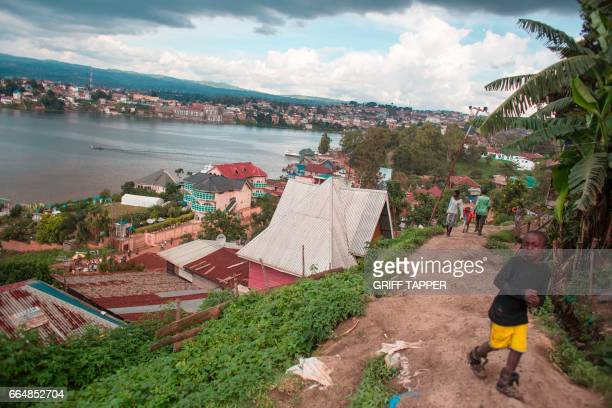 People walk near the port area of Bukavu in the Democratic Republic of Congo on March 31 2017 / AFP PHOTO / GRIFF TAPPER