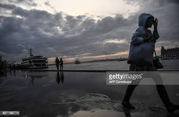 People walk near the port of Kadikoy at sunset on August 22 2017 in Istanbul / AFP PHOTO / BULENT KILIC