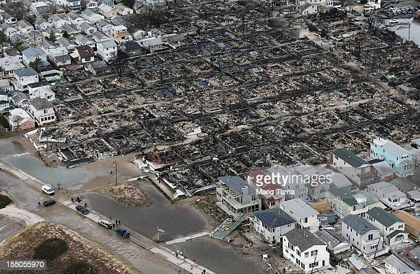 People walk near the remains of burned homes after Hurricane Sandy on October 31 2012 in the Breezy Point neighborhood of the Queens borough of New...