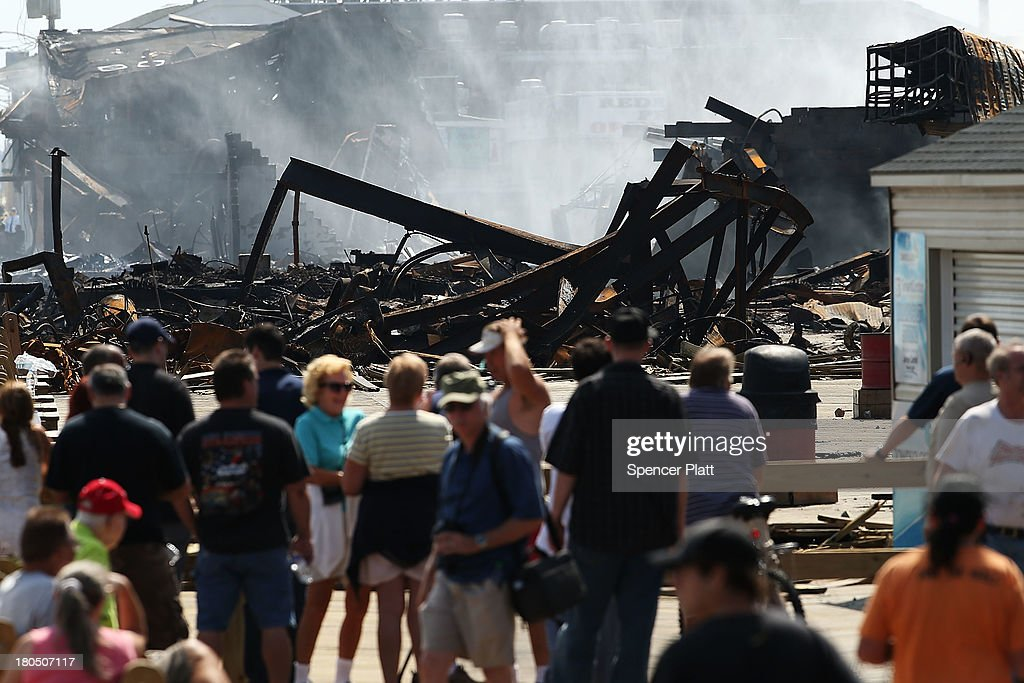 People walk near the scene of a massive fire that destroyed dozens of businesses along an iconic Jersey shore boardwalk on September 13, 2013 in Seaside Heights, New Jersey. The 6-alarm fire began in a frozen custard stand on the recently rebuilt boardwalk around 2:30 p.m. and quickly spread in high winds. While there were no injuries reported, many businesses that had only recently re-opened after Hurricane Sandy were destroyed in the blaze.