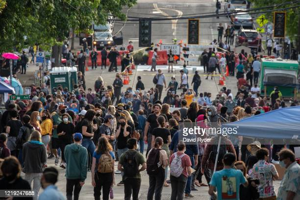 "People walk near the Seattle Police Departments East Precinct in the so-called ""Capitol Hill Autonomous Zone"" on June 10, 2020 in Seattle,..."