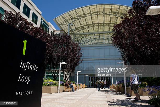 People walk near the visitors entrance at Apple Inc headquarters in Cupertino California US on Friday July 15 2011 Apple Inc is set to post a 69...