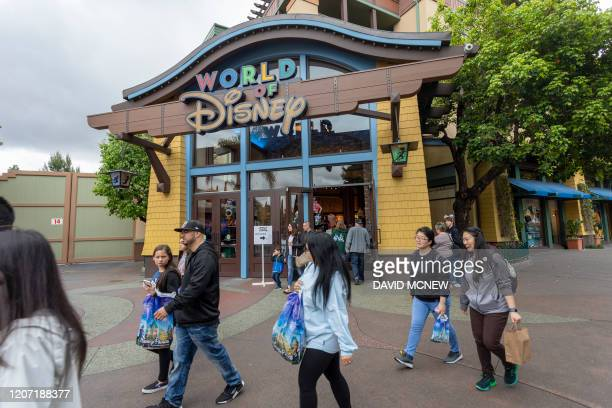 People walk near the World of Disney store in Downtown Disney District shopping mall which remains open on the first day of the closure of Disneyland...