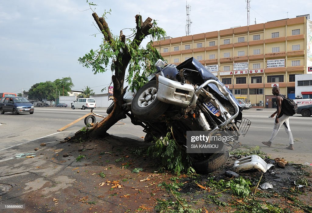 People walk near the wreck of a car after a road accident on November 24, 2012 in Abidjan.