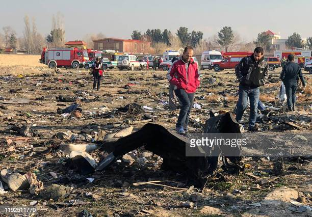 People walk near the wreckage after a Ukrainian plane carrying 176 passengers crashed near Imam Khomeini airport in Tehran early in the morning on...