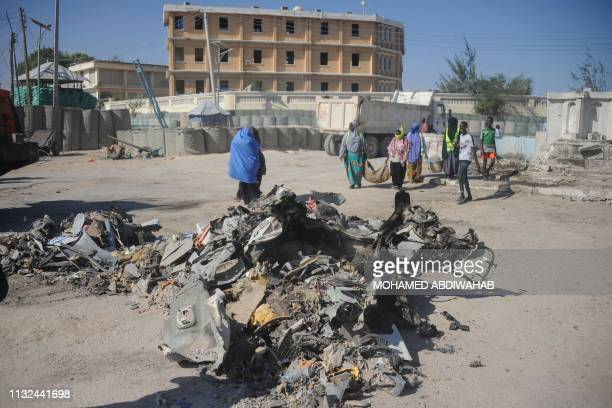 People walk near the wreckage of a car near the complex housing Somalia's ministries of works and labour stormed by AlShabaab militants in Somalia's...