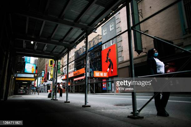 People walk near theaters at Times Square on August 8 2020 in New York City With more than four months NYC has closed some of their doors to combat...