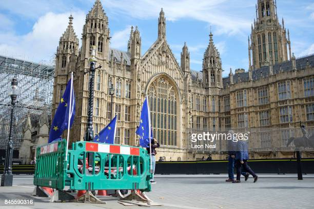 People walk near to EU flags attached to barriers outside the Houses of Parliament as MPs prepare to debate the EU Bill on September 11 2017 in...