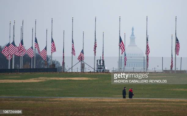 People walk near US flags flying at halfstaff at the Washington Monument with the capitol in the background in tribute to former US President George...