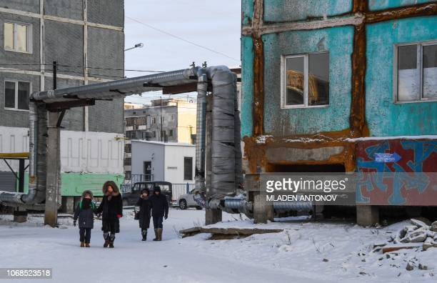 People walk next to a cracked panel apartment building in the eastern Siberian city of Yakutsk on November 26 2018 Many houses in Yakutsk are made up...